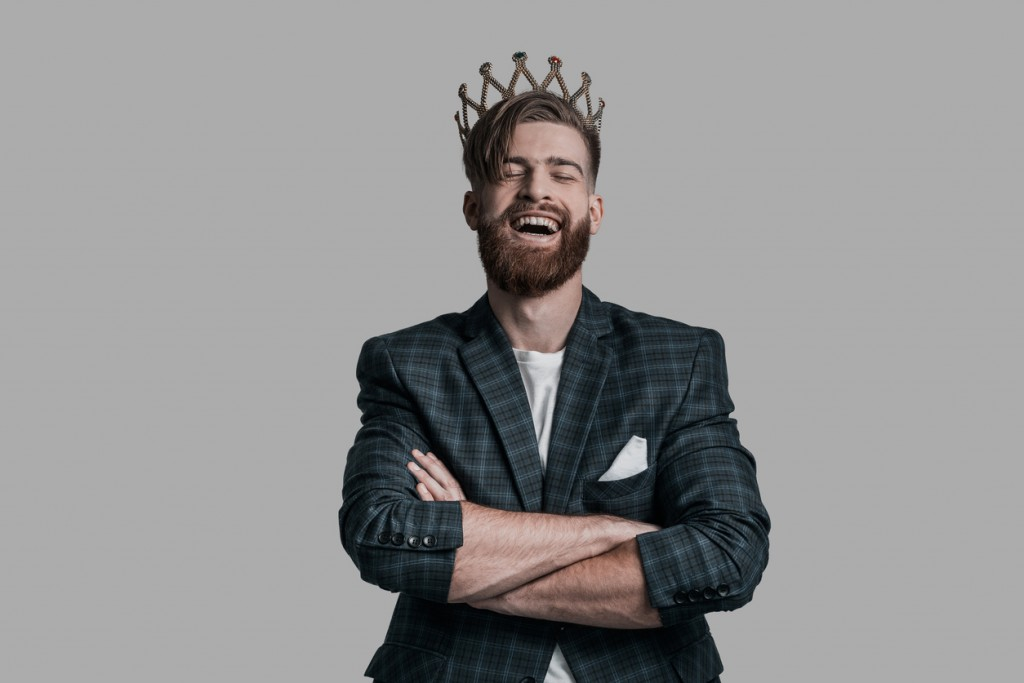 Young hipster wearing crown and keeping arms crossed while standing against grey background